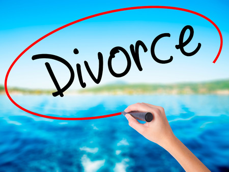 ex wife: Woman Hand Writing Divorce  on blank transparent board with a marker isolated over water background. Business concept. Stock Photo
