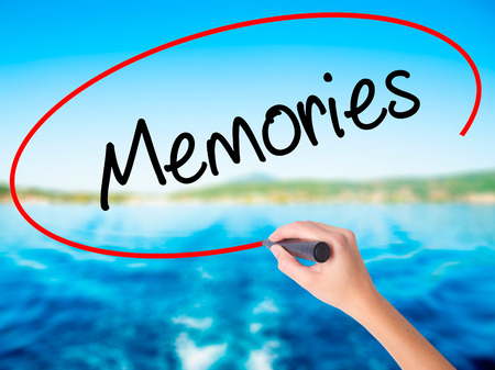 Woman Hand Writing Memories on blank transparent board with a marker isolated over water background. Business concept. Stock Photo