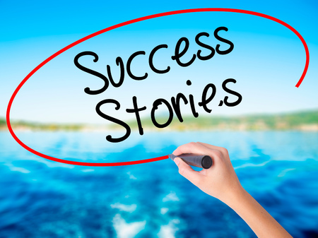 Woman Hand Writing Success Stories on blank transparent board with a marker isolated over water background. Business concept. Stock Photo