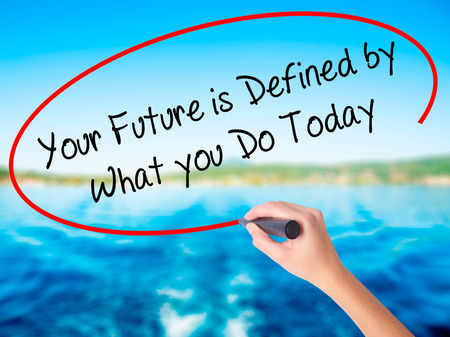 Woman Hand Writing Your Future is Defined by What you Do Today  on blank transparent board with a marker isolated over water background. Business concept. Stock Photo