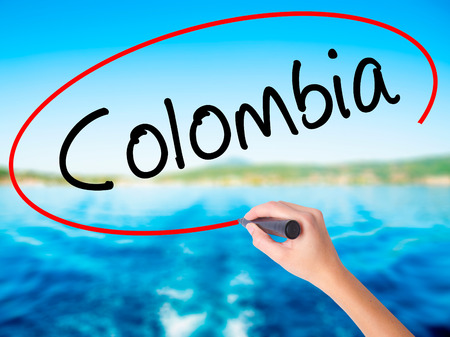 Woman Hand Writing Colombia with a marker over transparent board. Isolated on white. Travel, technology, internet concept. Stock Image