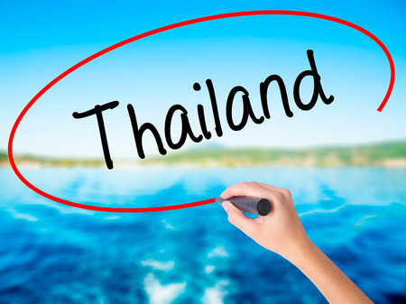 Woman Hand Writing Thailand  on blank transparent board with a marker isolated over water background. Business concept. Stock Photo