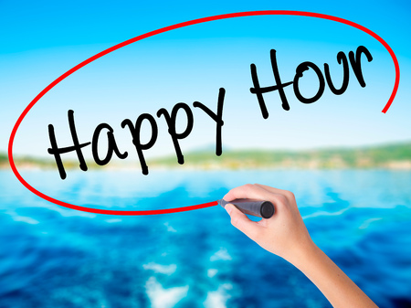 happyhour: Woman Hand Writing Happy Hour on blank transparent board with a marker isolated over water background. Business concept. Stock Photo