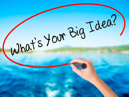 Woman Hand Writing Whats Your Big Idea?  on blank transparent board with a marker isolated over water background. Business concept. Stock Photo