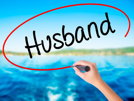 Woman Hand Writing Husband on blank transparent board with a marker isolated over water background. Business concept. Stock Photo