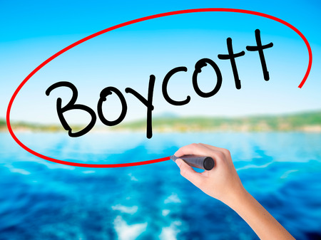 denying: Woman Hand Writing Boycott on blank transparent board with a marker isolated over water background. Business concept. Stock Photo