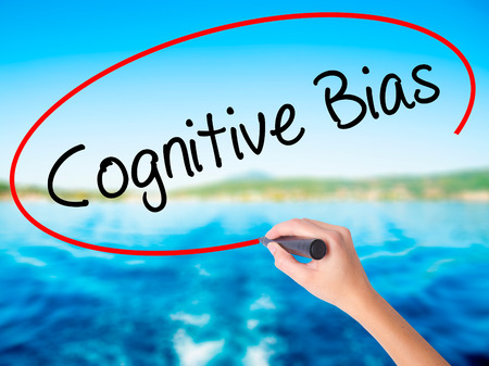 Woman Hand Writing Cognitive Bias on blank transparent board with a marker isolated over water background. Business concept. Stock Photo