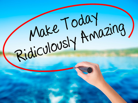 Woman Hand Writing Make Today Ridiculously Amazing on blank transparent board with a marker isolated over water background. Business concept. Stock Photo Imagens - 65069101