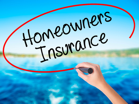 homeowners: Woman Hand Writing Homeowners Insurance on blank transparent board with a marker isolated over water background. Business concept. Stock Photo Stock Photo
