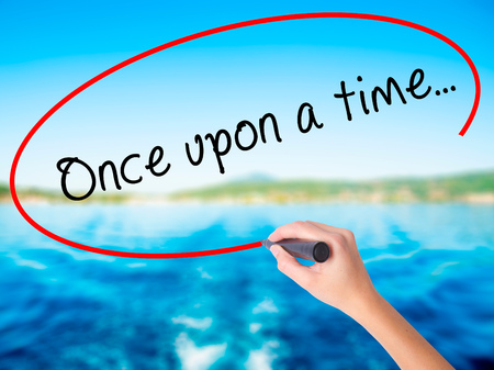 phrase novel: Woman Hand Writing Once upon a time... on blank transparent board with a marker isolated over water background. Business concept. Stock Photo