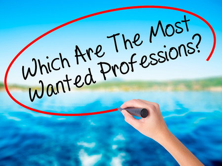 most talent: Woman Hand Writing Which Are The Most Wanted Professions? on blank transparent board with a marker isolated over water background. Business concept. Stock Photo