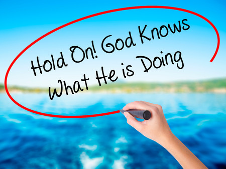 confessing: Woman Hand Writing Hold On! God Knows What He is Doing on blank transparent board with a marker isolated over water background. Business concept. Stock Photo Stock Photo