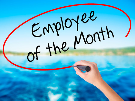 recognizing: Woman Hand Writing Employee of the Month  on blank transparent board with a marker isolated over water background. Business concept. Stock Photo Stock Photo