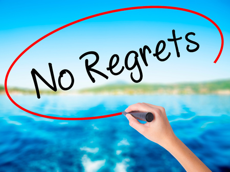 Woman Hand Writing No Regrets on blank transparent board with a marker isolated over water background. Business concept. Stock Photo