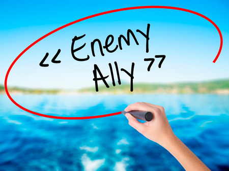 interdependence: Woman Hand Writing Enemy - Ally on blank transparent board with a marker isolated over water background. Business concept. Stock Photo