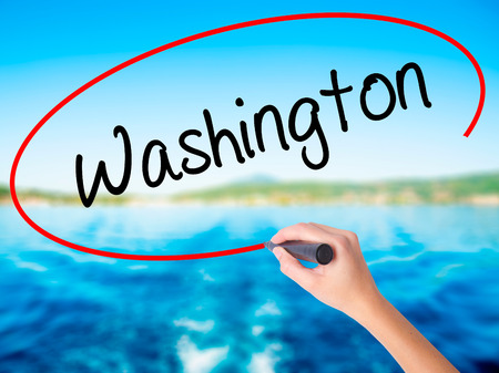 Woman Hand Writing Washington  on blank transparent board with a marker isolated over water background. Business concept. Stock Photo