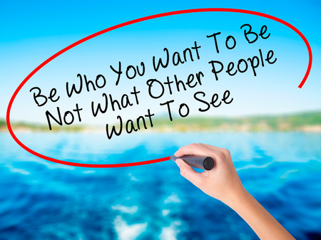 advise: Woman Hand Writing Be Who You Want To Be Not What Other People Want To See on blank transparent board with a marker isolated over water background. Business concept. Stock Photo