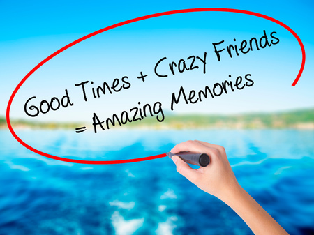 positiveness: Woman Hand Writing Good Times + Crazy Friends = Amazing Memories on blank transparent board with a marker isolated over water background. Business concept. Stock Photo