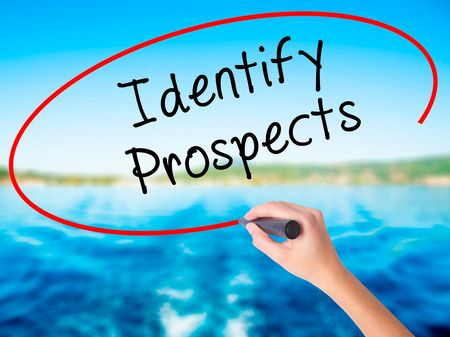 Woman Hand Writing Identify Prospects on blank transparent board with a marker isolated over water background. Business concept. Stock Photo