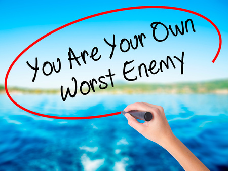 the worst: Woman Hand Writing You Are Your Own Worst Enemy on blank transparent board with a marker isolated over water background. Business concept. Stock Photo Stock Photo