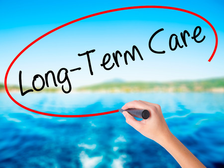 Woman Hand Writing Long-Term Care on blank transparent board with a marker isolated over water background. Business concept. Stock Photo