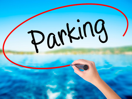 Woman Hand Writing Parking on blank transparent board with a marker isolated over water background. Business concept. Stock Photo