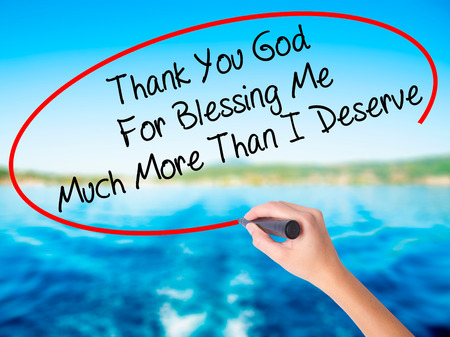 universal love: Woman Hand Writing Thank You God For Blessing Me Much More Than I Deserve on blank transparent board with a marker isolated over water background. Business concept. Stock Photo Foto de archivo