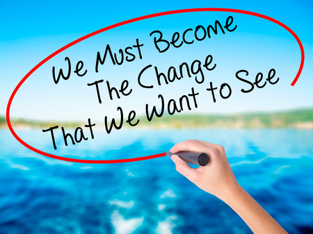 Woman Hand Writing We Must Become The Change That We Want to See on blank transparent board with a marker isolated over water background. Business concept. Stock Photo