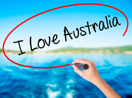 Woman Hand Writing I Love Australia on blank transparent board with a marker isolated over water background. Business concept. Stock Photo