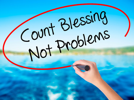 preachment: Woman Hand Writing Count Blessing Not Problems on blank transparent board with a marker isolated over water background. Business concept. Stock Photo
