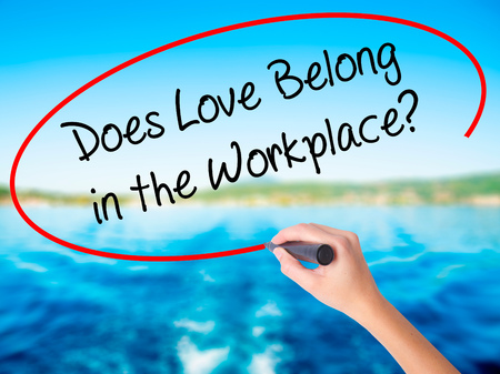 belong: Woman Hand Writing Does Love Belong in the Workplace? on blank transparent board with a marker isolated over water background. Business concept. Stock Photo Stock Photo