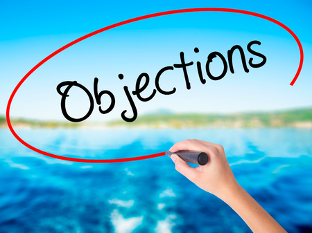 objections: Woman Hand Writing Objections  on blank transparent board with a marker isolated over water background. Business concept. Stock Photo Stock Photo