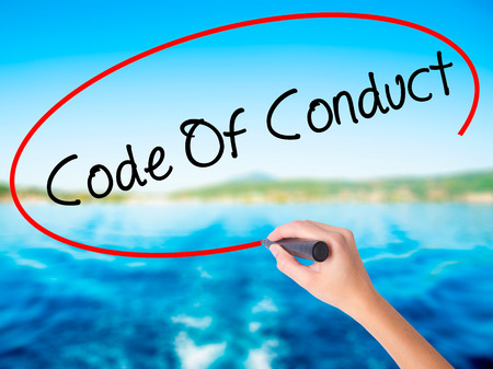work ethic responsibilities: Woman Hand Writing Code Of Conduct on blank transparent board with a marker isolated over water background. Business concept. Stock Photo Stock Photo