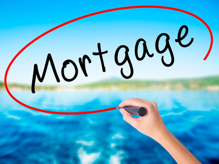 Woman Hand Writing Mortgage on blank transparent board with a marker isolated over water background. Business concept. Stock Photo