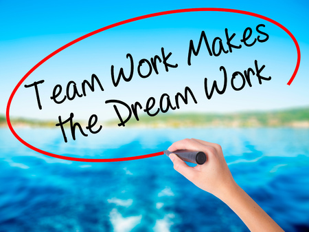 motto: Woman Hand Writing Team Work Makes the Dream Work on blank transparent board with a marker isolated over water background. Business concept. Stock Photo Stock Photo