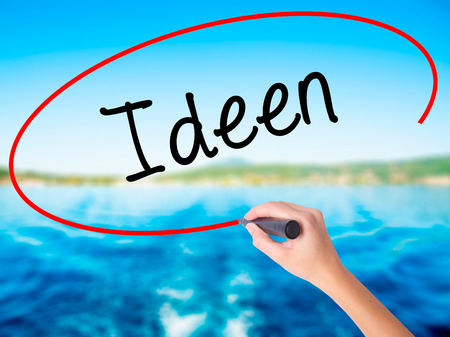 Woman Hand Writing Ideen (Ideas in German)  on blank transparent board with a marker isolated over water background. Business concept. Stock Photo