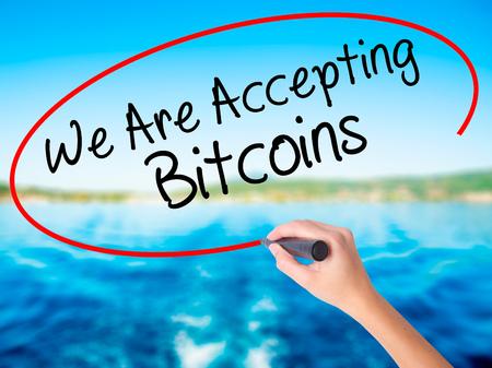 Femme main écrit Nous acceptons les Bitcoins sur un tableau transparent blanc avec un marqueur isolé sur fond de l'eau. Concept d'entreprise Photo en stock Banque d'images