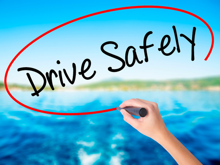 Woman Hand Writing  Drive Safely on blank transparent board with a marker isolated over water background. Business concept. Stock Photo