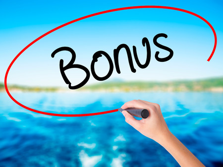 Woman Hand Writing Bonus on blank transparent board with a marker isolated over water background. Business concept. Stock Photo