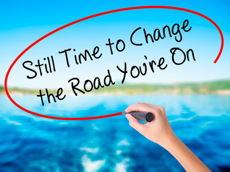 next horizon: Woman Hand Writing Still Time to Change the Road Youre On on blank transparent board with a marker isolated over water background. Business concept. Stock Photo
