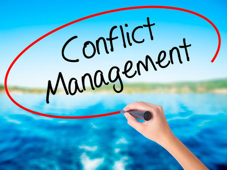 Woman Hand Writing Conflict Management on blank transparent board with a marker isolated over water background. Business concept. Stock Photo