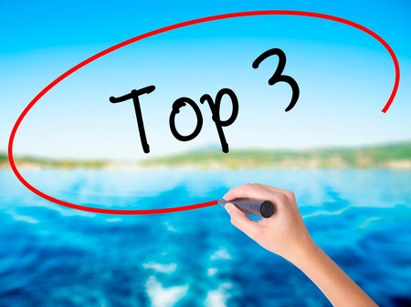 Woman Hand Writing Top 3 on blank transparent board with a marker isolated over water background. Business concept. Stock Photo