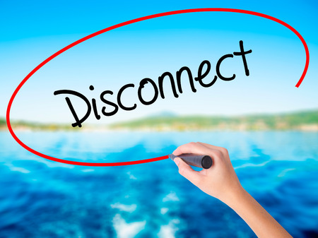 disconnection: Woman Hand Writing Disconnect on blank transparent board with a marker isolated over water background. Business concept. Stock Photo Stock Photo