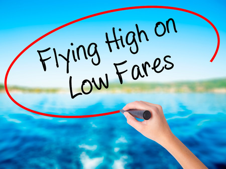 Woman Hand Writing Flying High on Low Fares on blank transparent board with a marker isolated over water background. Business concept. Stock Photo