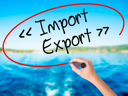 Woman Hand Writing Import - Export on blank transparent board with a marker isolated over water background. Business concept. Stock Photo