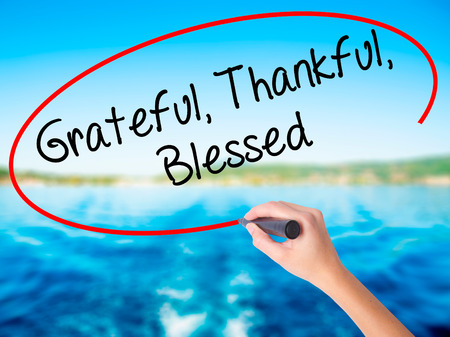 humility: Woman Hand Writing  Grateful Thankful Blessed on blank transparent board with a marker isolated over water background. Business concept. Stock Photo