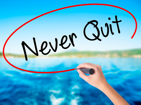 Woman Hand Writing Never Quit with a marker over transparent board. Isolated on background. Business, technology, internet concept. Stock  Photo