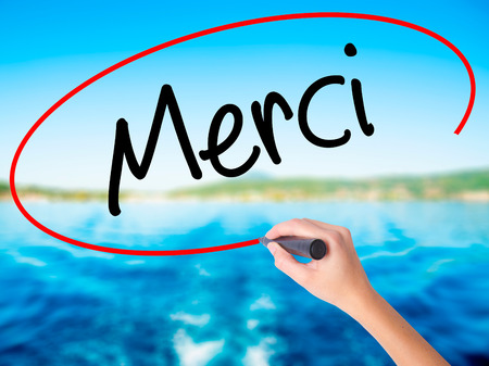 Woman Hand Writing Merci  (Thank You In French) on blank transparent board with a marker isolated over water background. Business concept. Stock Photo