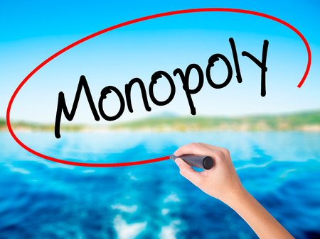Woman Hand Writing Monopoly on blank transparent board with a marker isolated over water background. Business concept. Stock Photo