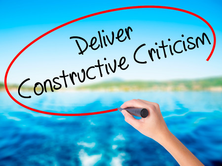Woman Hand Writing Deliver Constructive Criticism on blank transparent board with a marker isolated over water background. Business concept. Stock Photo